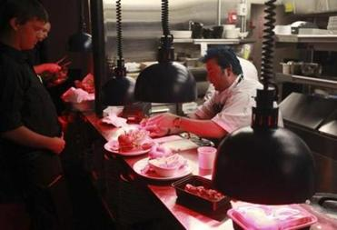 Jason Santos (blue hair) at work at his new restaurant in Boston's Theatre District.